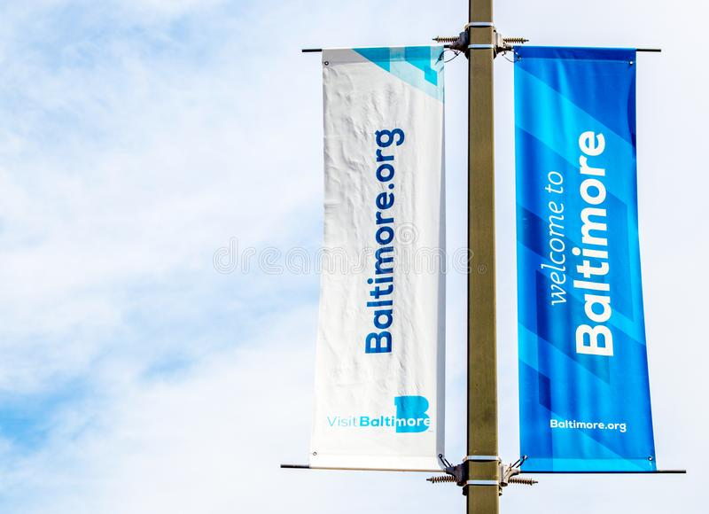 Welcome banners on a lamp post in Baltimore`s Inner Harbor. Bright blue and white welcome banners on a lamp post in Baltimore`s Inner Harbor on a sunny day with royalty free stock photo
