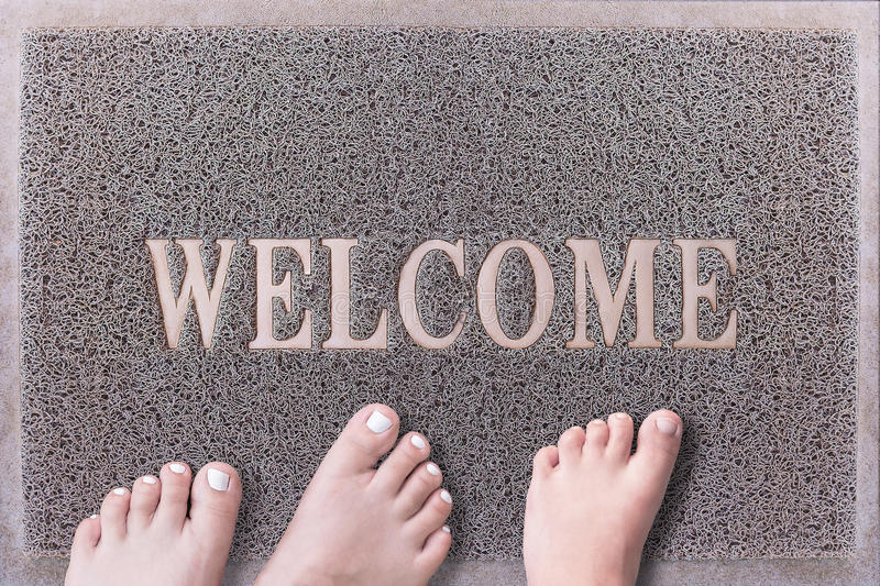 Welcome Door Mat With Three Feet. Friendly Grey Door Mat Closeup with Bare Feet Standing. Welcome Carpet. royalty free stock image