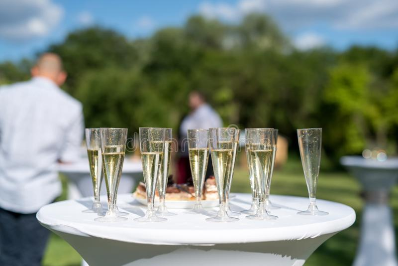 Welcome drink, view of glasses filled with champagne on a table in a garden. Selective fokus royalty free stock photography