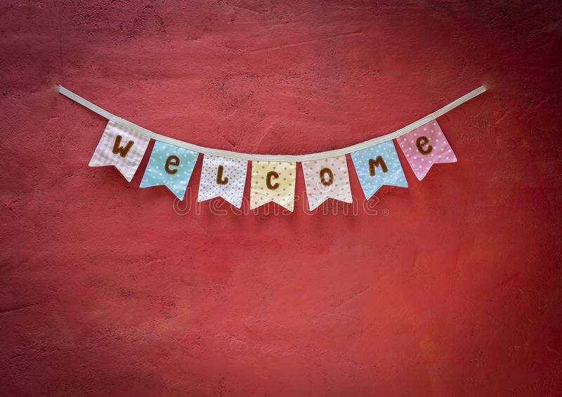 Welcome fabric flag design on red cement wall texture background royalty free stock images