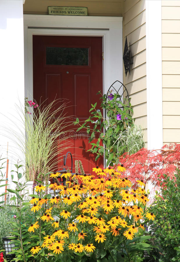 Welcome front door. Bright red front door surrounded by colorful flowers. Sign above door says: Friends welcome, relatives by appointment stock image