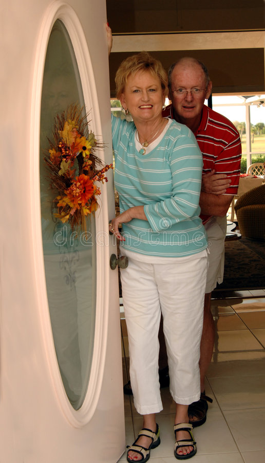 Welcome home. A smiling senior couple standing just inside their open front door