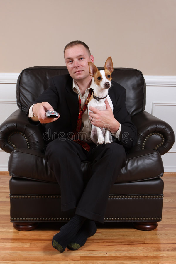 Welcome Home. A man relaxing with his dog and his remote control after a long day at work stock image