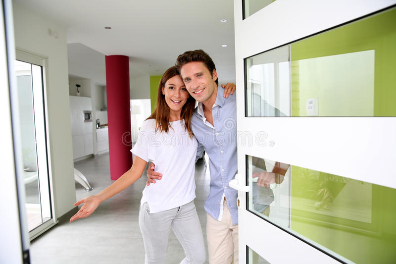 Welcome home. Cheerful couple inviting people to enter in home