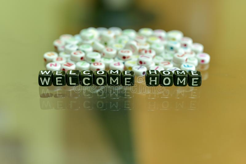WELCOME HOME  written with Acrylic Black cube with white Alphabet Beads on the Glass Background. WELCOME HOME written with Acrylic Black cube with white Alphabet stock photo