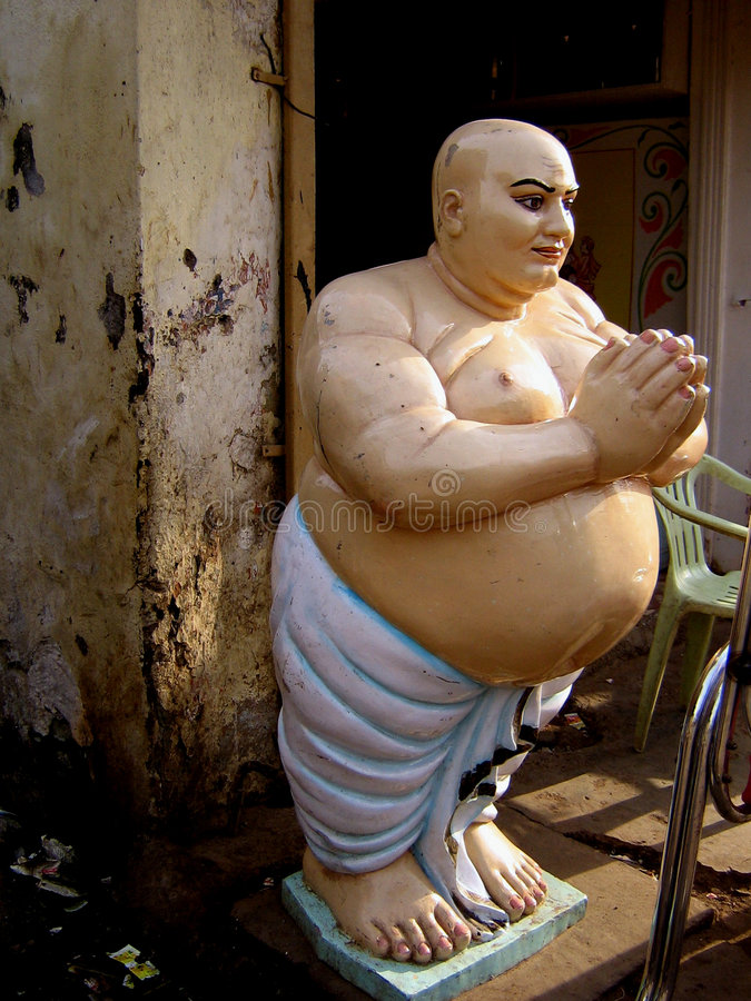 Welcome Idol. An idol of a fat bald man in an Indian Welcoming pose stands in an artists workshop stock photography