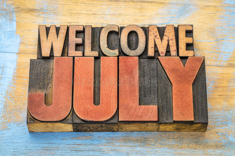 Welcome July word abstract in wood type royalty free stock image