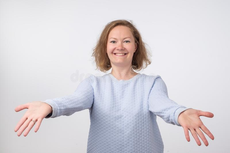 Welcome or Nice to meet you concept. European woman with stretched hands handshake. stock photo
