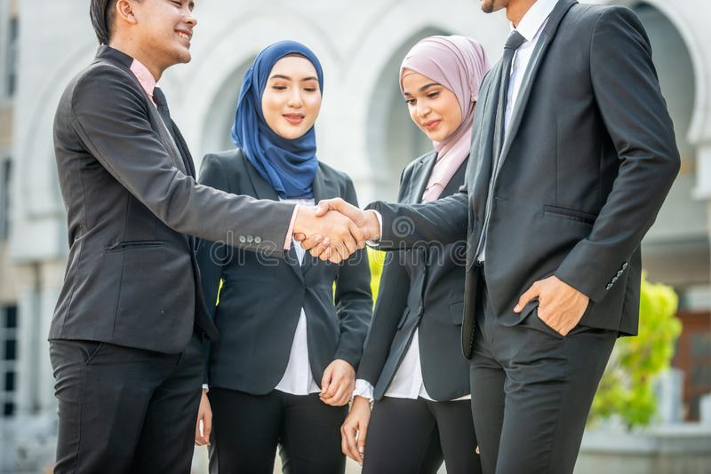 Welcome onboard! Muslim Asian business people shake hands. Welcome onboard! Muslim Asian business people shaking hands with new partner, business co-working stock photography