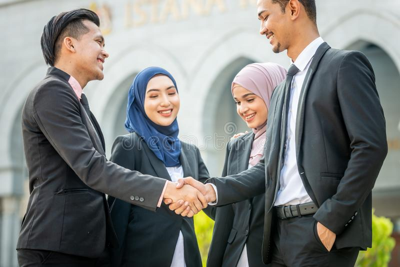 Welcome onboard! Muslim Asian business people shakes hand. Welcome onboard! Muslim Asian business people shaking hands with new partner, business co-working royalty free stock photography