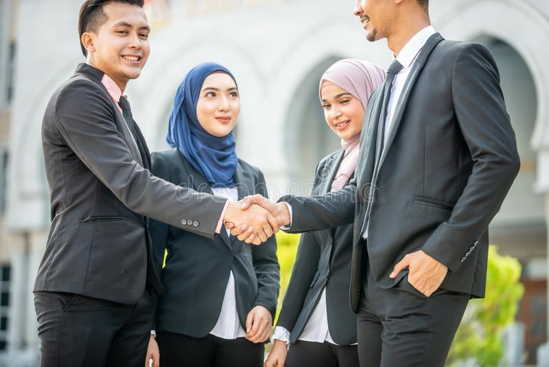Welcome onboard! Muslim Asian business people shaking hands with new partner, business co-working teamwork concept stock photography