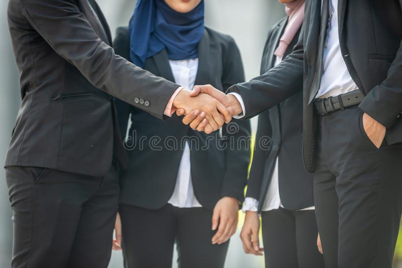 Welcome onboard! Muslim Asian business people shaking hands with new partner, business co-working teamwork concept.  royalty free stock image