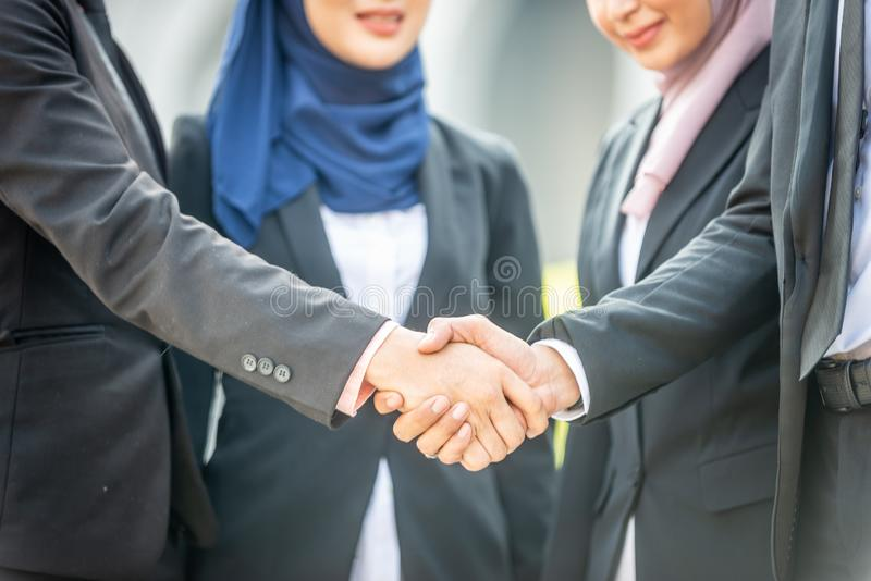 Congratulations! Muslim Asian business people shakes hand. Welcome onboard! Muslim Asian business people shaking hands with new partner, business co-working royalty free stock photography