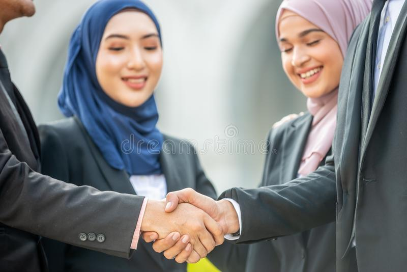 Congratulations! Muslim Asian business people shakes hand. Welcome onboard! Muslim Asian business people shaking hands with new partner, business co-working stock photo