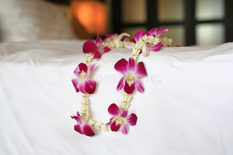 Welcome orchids garland place on the bed of luxury hotel in thailand royalty free stock photo