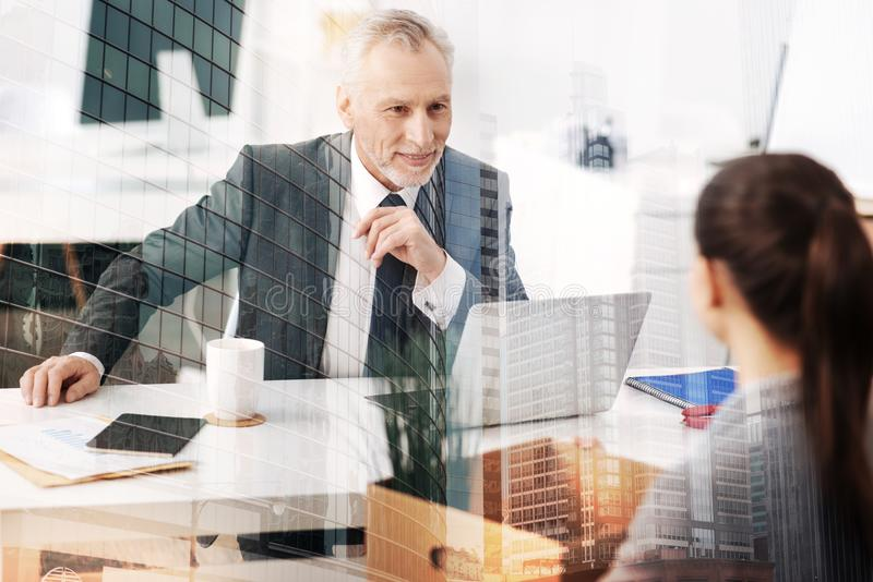 Positive adult boss having a talk with a new employee stock images