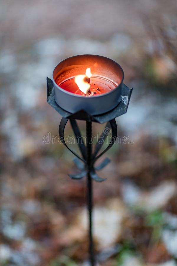 Welcome outdoor candle in a tall metallic holder. Welcome to an outdoor party candle in a tall metallic holder burning with dark orange wax stock photo
