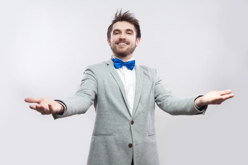 Welcome. Portrait of happy handsome bearded man in casual grey suit and blue bow tie standing with raised arms and looking at stock photos