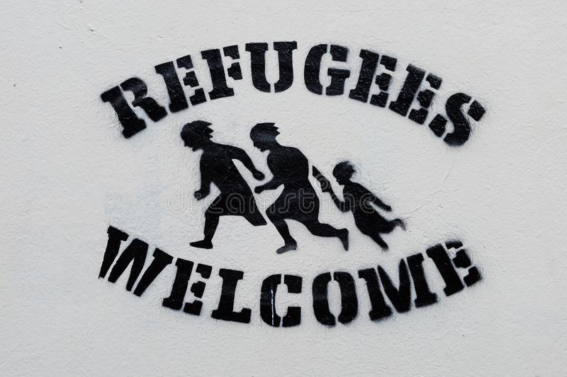 Welcome Refugees Text Stencil Print On White Wall Stock Photo