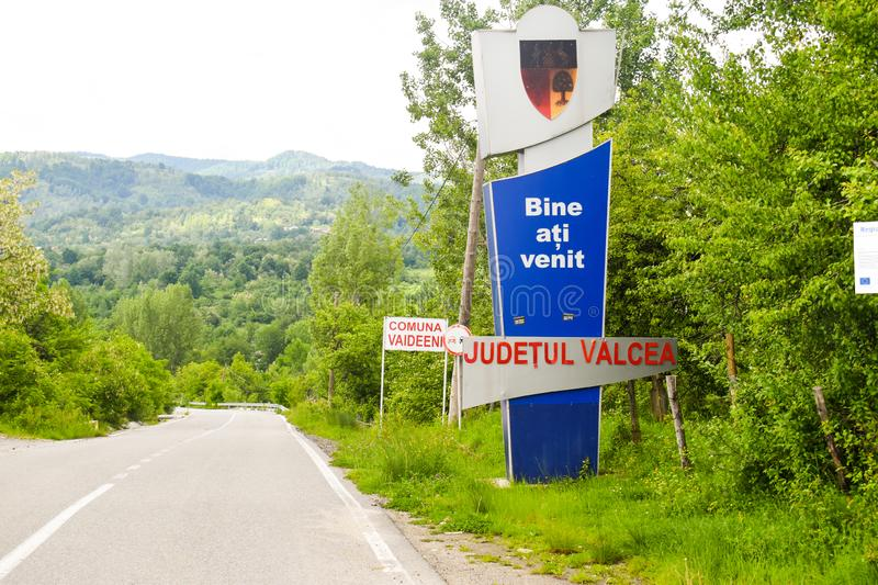 Welcome sign next to the asphalt road in the village Vaideeni of Valcea County. Vaideeni, Romania - 23.05.2019 royalty free stock image