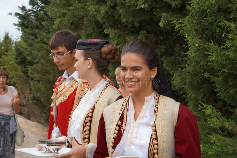 Welcome smiling girl. One girl from Latvia trying to dance with beautiful dancers and singers at the nice folk style evening meal in Montenegro stock photo