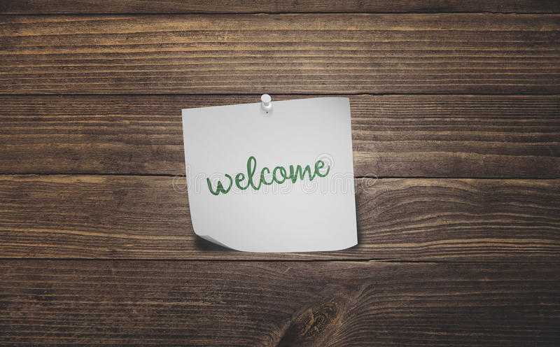 Welcome sticky note. Word welcome on white sticky note paper on vintage rustic wood planks floor stock photo