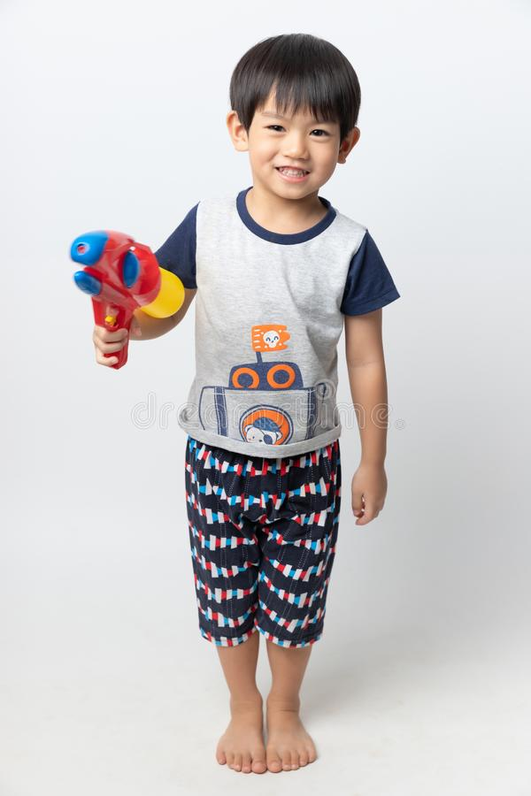 Welcome Thailand Songkran festival, Portrait of Asian boy smiled with water gun on white background royalty free stock photography