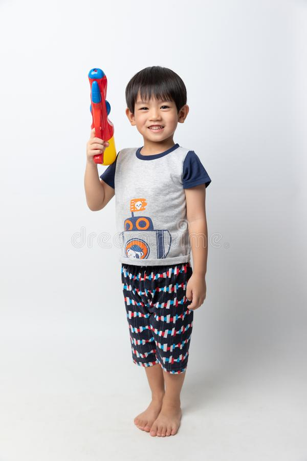 Welcome Thailand Songkran festival, Portrait of Asian boy smiled with water gun on white background royalty free stock image