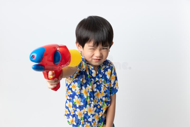 Welcome Thailand Songkran festival, Portrait of Asian boy wearing flower shirt smiled with water gun on white background royalty free stock photo