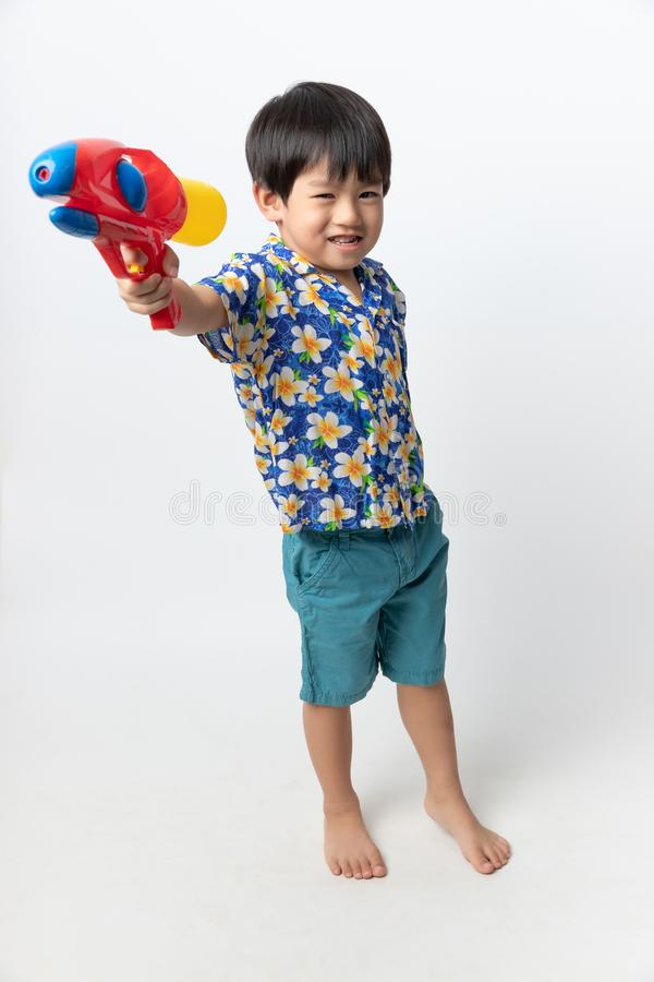 Welcome Thailand Songkran festival, Portrait of Asian boy wearing flower shirt smiled with water gun on white background stock image