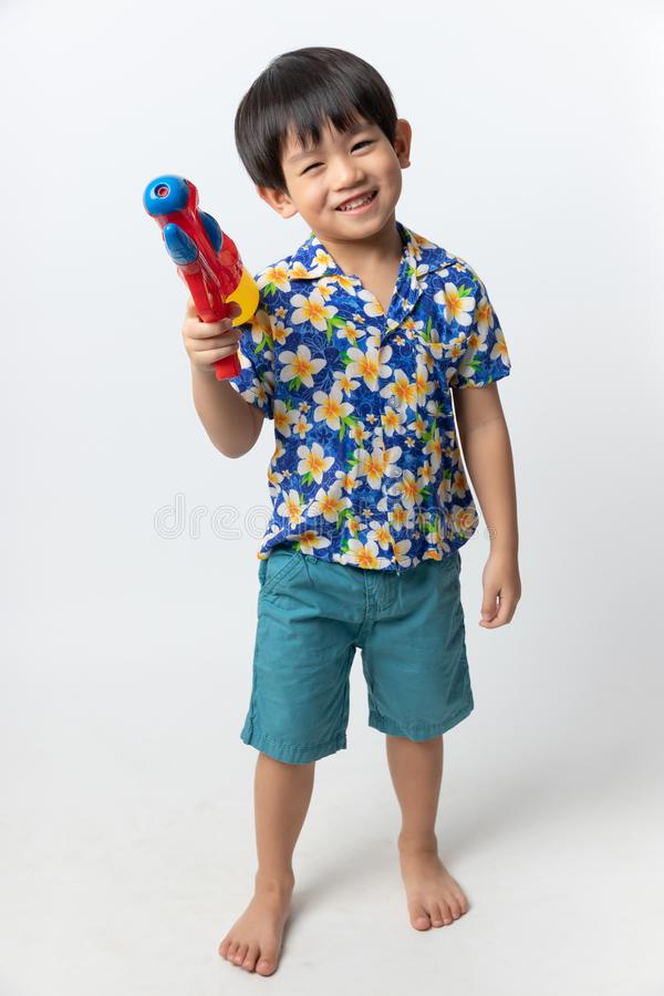 Welcome Thailand Songkran festival, Portrait of Asian boy wearing flower shirt smiled with water gun on white background royalty free stock images