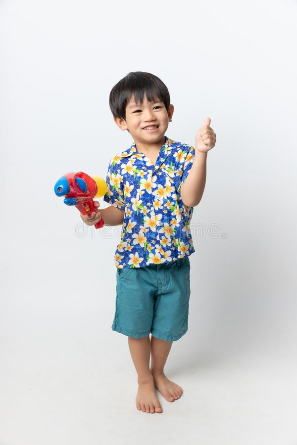 Welcome Thailand Songkran festival, Portrait of Asian boy wearing flower shirt smiled with water gun on white background stock photography