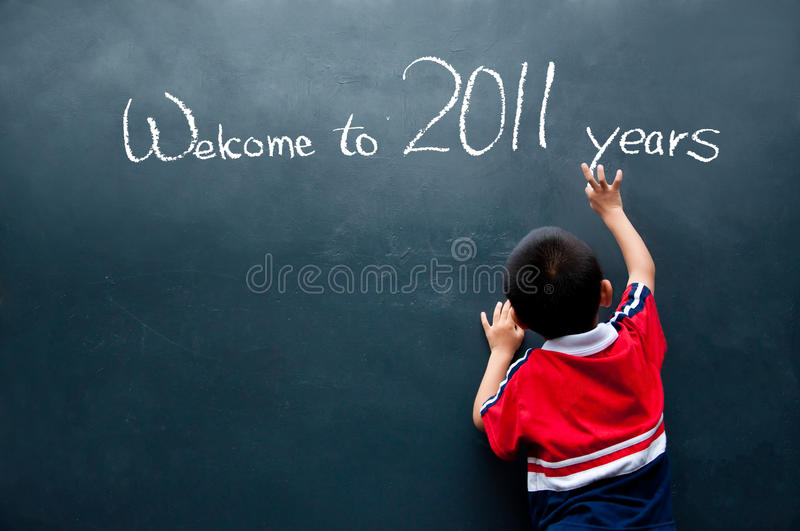 Welcome to 2011 years. Boy writing on the wall and welcome to 2011 years royalty free stock images