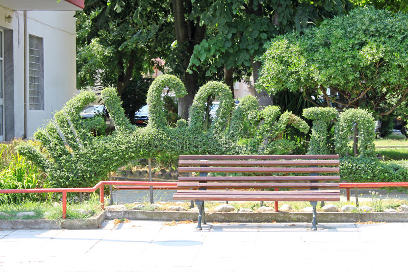 Welcome To. Bushes cut as words Welcome to. Street and home decoration. Empty wooden bench in the foreground royalty free stock photo