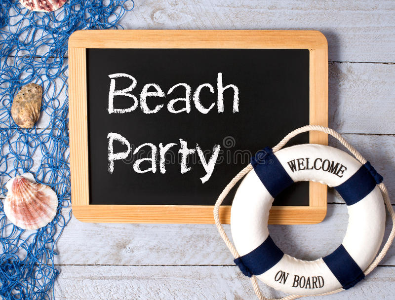 Welcome to beach party. Text 'Beach Party' in white text on black chalkboard beside a ship's buoy marked 'welcome on board' with fish net, seashells and white royalty free stock photos