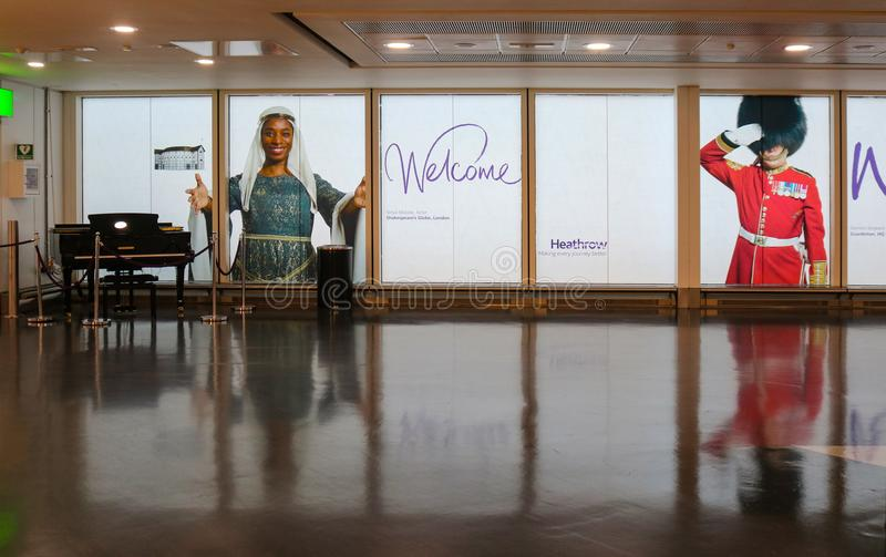 Welcome to Heathrow Airport - View with grand piano and images of multicultural people greeting travelers entering Heathrow London stock photos