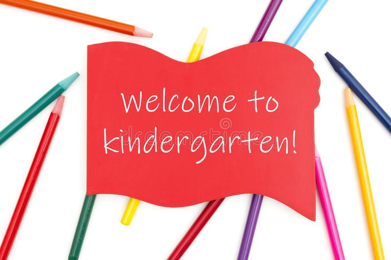 Welcome to kindergarten message on red wood sign with colored watercolor pencils. Welcome to kindergarten on red wood sign with colored watercolor pencils over royalty free stock photography