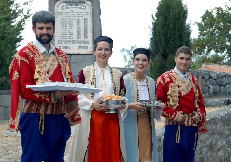 Welcome to Montenegro. Twp couples in national Montenegro costume at the nice folk style evening meal in Montenegro stock photography