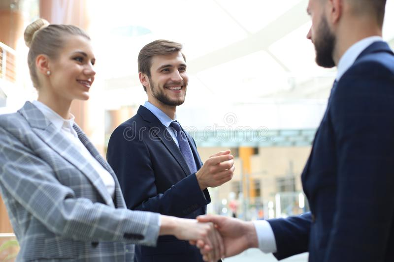 Welcome to our team. Young modern businessmen shaking hands while working in the creative office.  stock images
