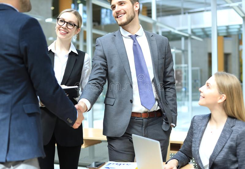 Welcome to our team. Young modern businessmen shaking hands while working in the creative office.  stock image