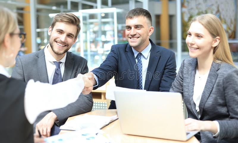 Welcome to our team. Young modern businessmen shaking hands while working in the creative office.  stock photography