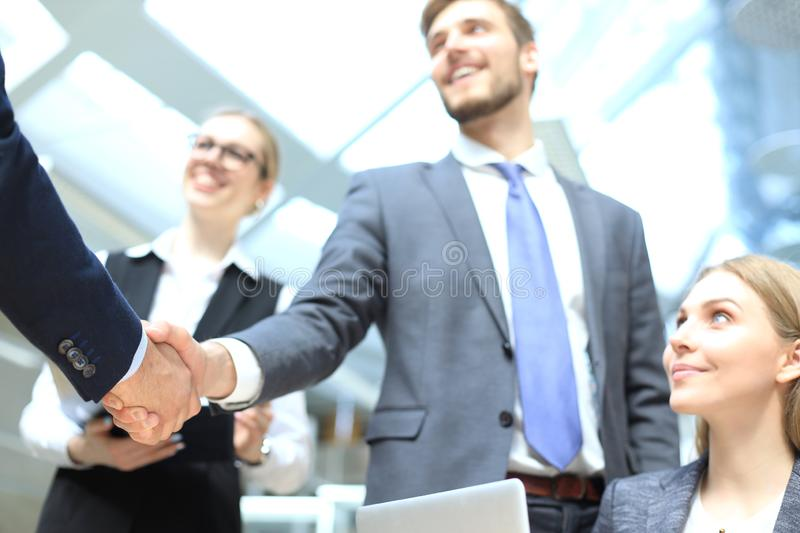 Welcome to our team. Young modern businessmen shaking hands while working in the creative office.  royalty free stock photos