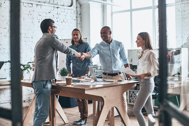 Welcome to our team. Young modern men in smart casual wear shaking hands while standing with their colleagues in the board room royalty free stock images