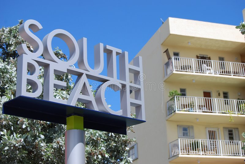 Welcome to South Beach. Sign at the eastern end of the Venetia Causeway a main connector between Miami and Miami Beach. A vintage lowrise condo is in the stock photo