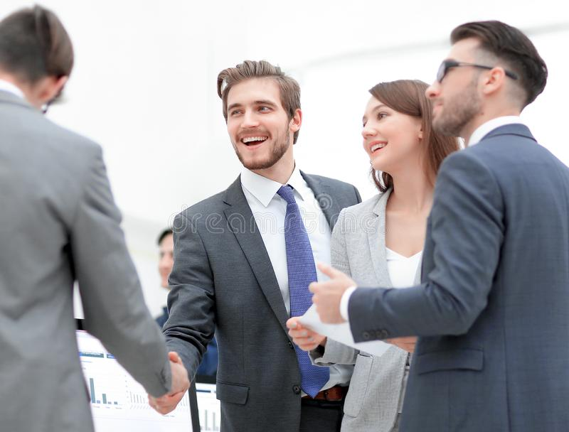 Business people shaking hands, finishing up a meeting. Welcome to team! Two men shaking hands and looking at each other with smile while their co workers sitting stock images