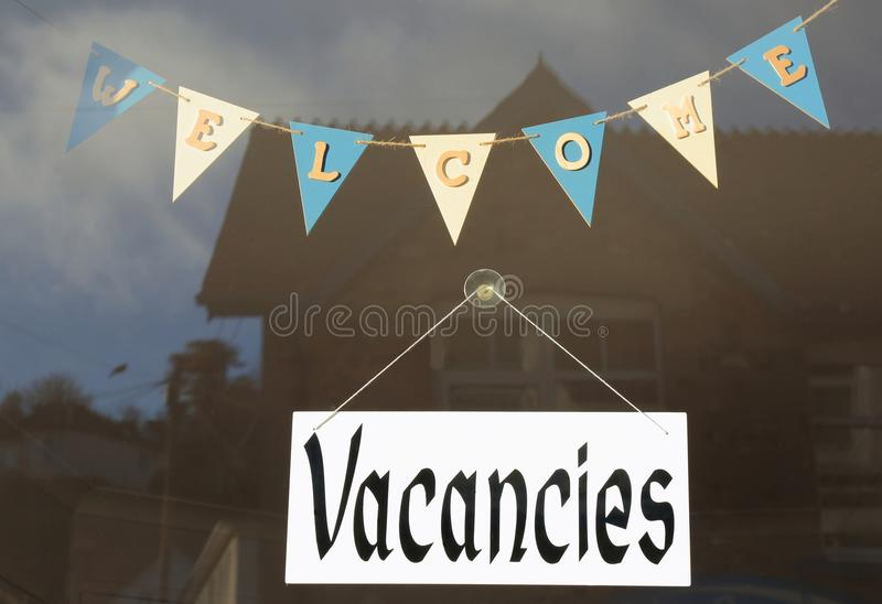 Vacancies. Welcome and vacancies signs in shop window stock images