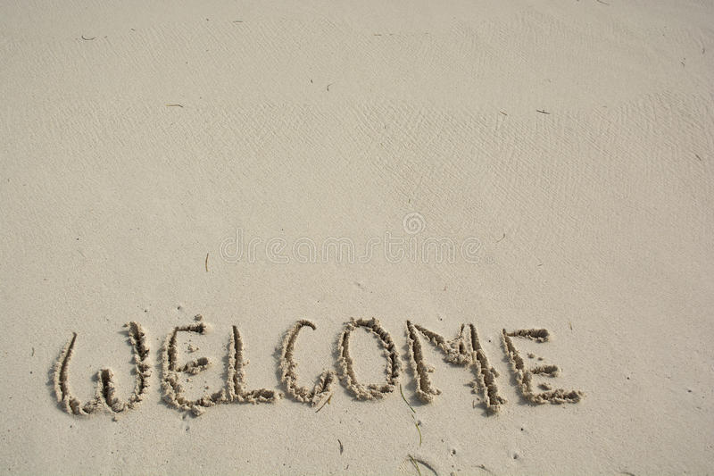 Welcome written in a tropical beach. Welcome written in a sandy tropical beach royalty free stock image