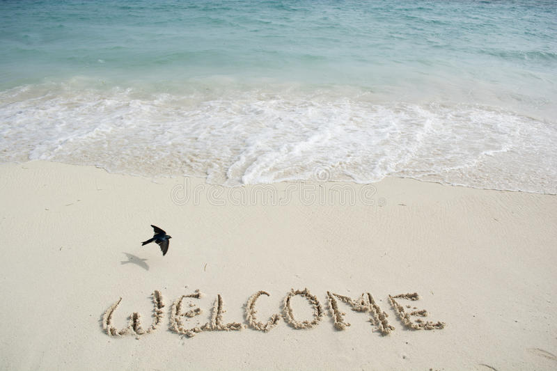 Welcome written in a tropical beach. Welcome written in a sandy tropical beach stock photography