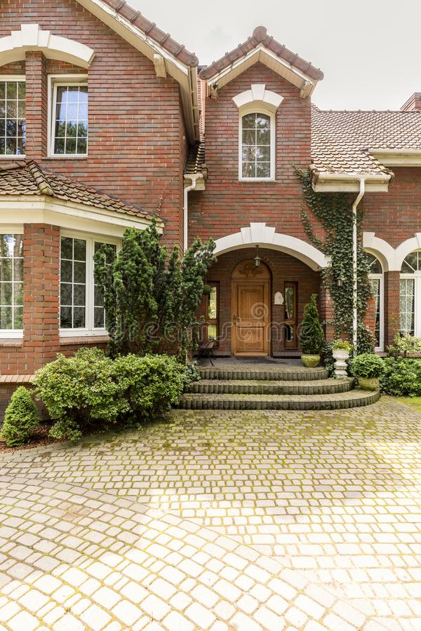 A welcoming entryway with ornamented wooden door, side windows a. Nd evergreens in a red brick stylish house. Empty cobbled path in a front royalty free stock photos
