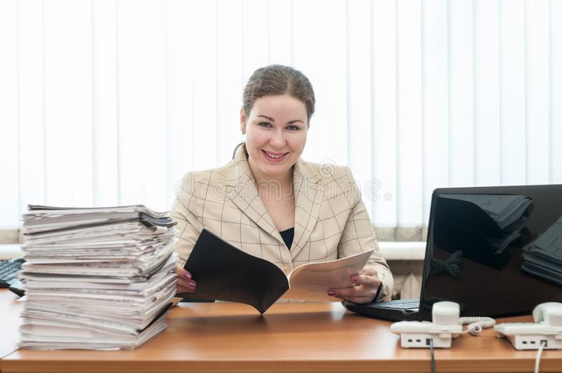 Welcoming receptionist a woman looking at camera with schedule or list royalty free stock images